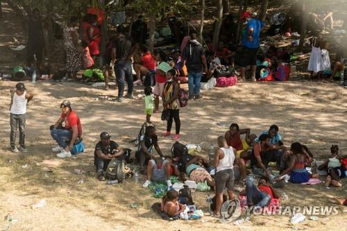 텍사스주 델리오와 멕시코 시우다드아쿠냐를 연결하는 델리오 국경 다리 아래에 15일 이민자들이 모여있다. [사진 출처: 로이터 / 연합뉴스]