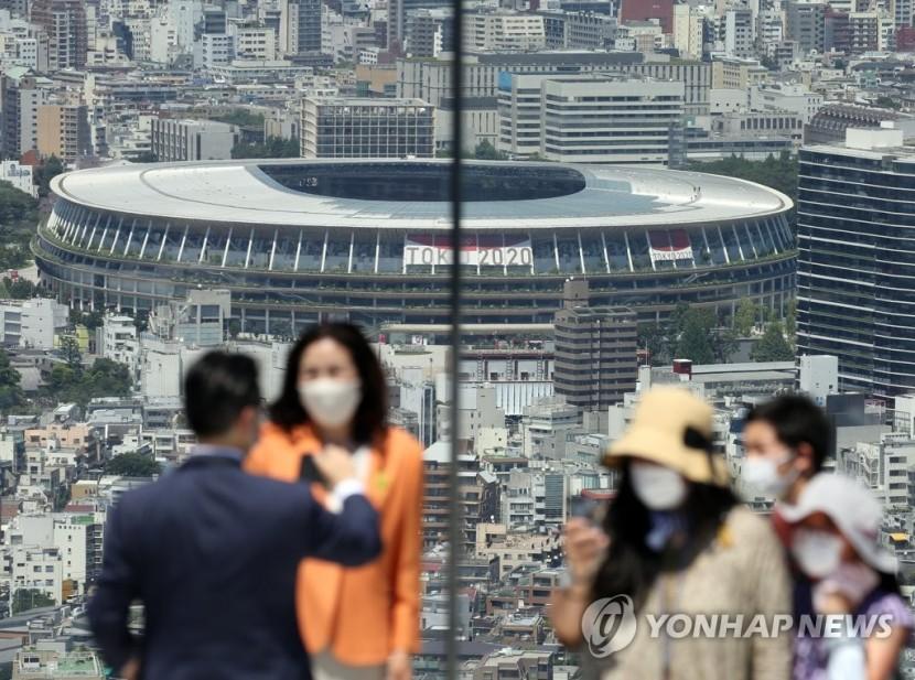 도쿄올림픽 개막식을 이틀 앞둔 21일 오후 일본 도쿄도(東京都)의 한 고층 건물 전망대 방문객들이 도심을 배경으로 기념사진을 찍고 있다.